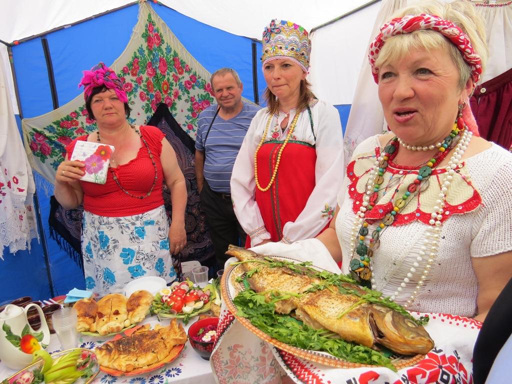 Дирекор Холмовского ДК Анна Шаркова угощает гостей жареной рыбой